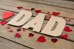 Fermez-vous du texte de papa avec des formes de coeur sur la table Photo stock