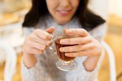 Fermez-vous du thé potable de jeune femme heureuse au café Photographie stock