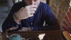 Fermez-vous du thé potable de l'homme à l'intérieur du restaurant chinois banque de vidéos