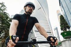 Fermez-vous du vélo sportif d'équitation de sportif à côté de l'architecture moderne photo stock