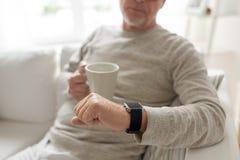 Fermez-vous du vieil homme avec la tasse regardant la montre-bracelet Photos stock