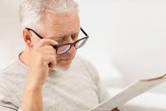 Fermez-vous du vieil homme en verres lisant le journal Image stock