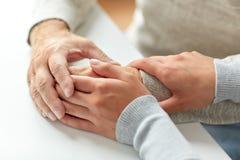 Fermez-vous du vieil homme et de la jeune femme tenant des mains Photo stock