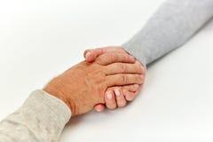 Fermez-vous du vieil homme et de la jeune femme tenant des mains Image libre de droits