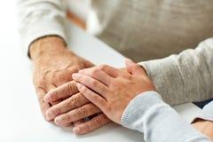 Fermez-vous du vieil homme et de la jeune femme tenant des mains Image stock