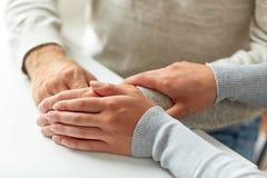 Fermez-vous du vieil homme et de la jeune femme tenant des mains Images stock
