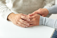 Fermez-vous du vieil homme et de la jeune femme tenant des mains Photographie stock