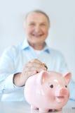Fermez-vous du vieil homme mettant la pièce de monnaie dans la tirelire Photo stock