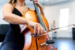 Fermez-vous du violoncelle avec l'arc dans des mains photographie stock