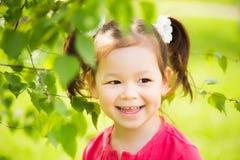 Fermez-vous du visage de l'enfant jouant le cache-cache dehors en parc photo stock