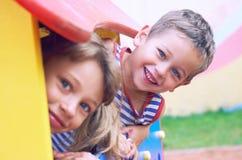 Fermez-vous du visage de sourire de childs se cachant derrière l'élément en bois de la glissière au terrain de jeu le jour d'été photos libres de droits