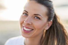 Fermez-vous du visage de sourire heureux de jeune femme photographie stock libre de droits