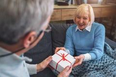 Fermez-vous et coupez la vue du vieil homme donnant un cadeau à l'épouse de hai Il l Photos stock
