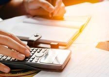 Fermez-vous, homme d'affaires ou comptable d'avocat travaillant sur des comptes utilisant une calculatrice et écrivant sur des do Photo stock