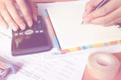 Fermez-vous, homme d'affaires ou comptable d'avocat travaillant sur des comptes utilisant une calculatrice et écrivant sur des do Photos stock