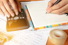 Fermez-vous, homme d'affaires ou comptable d'avocat travaillant sur des comptes utilisant une calculatrice et écrivant sur des do Photos libres de droits