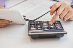 Fermez-vous, homme d'affaires ou comptable d'avocat travaillant sur des comptes utilisant une calculatrice et écrivant sur des do Photo libre de droits