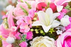 Fermez-vous jusqu'au rose en plastique coloré fleurit lilly avec des roses et l Photo stock