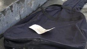Fermez-vous pour des astuces se trouvant sur la caisse noire de guitare sur le fond gris de trottoir Monnaie fiduciaire russe se  photos libres de droits
