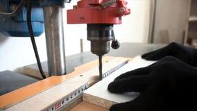 Fermez-vous pour le détail des mains travaillant à la foreuse à l'atelier de menuiserie longueur Mains d'homme fonctionnant avec image stock