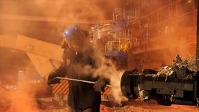 Fermez-vous pour un travailleur utilisant le four de nettoyage uniforme à l'usine métallurgique Longueur courante Fondeur dans le photos stock