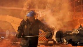 Fermez-vous pour un travailleur utilisant le four de nettoyage uniforme à l'usine métallurgique Longueur courante Fondeur dans le image libre de droits