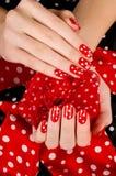Fermez-vous sur de belles mains femelles avec la manucure rouge mignonne avec les points blancs. Photos stock