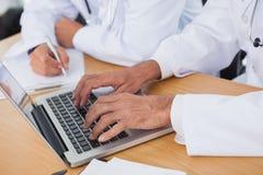 Fermez-vous sur des mains de médecins dactylographiant sur l'ordinateur portable photographie stock