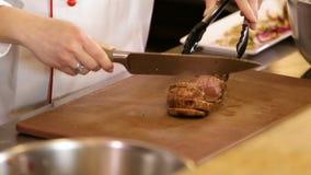Fermez-vous sur des mains tenant la viande cuite sur une planche à découper, coupant en tranches la viande cuite en tranches clips vidéos