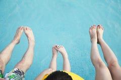 Fermez-vous sur des pieds sur la jeune famille dans la piscine Images libres de droits