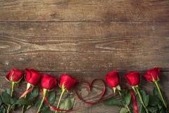 Fermez-vous sur des roses au-dessus de table en bois avec le coeur de ruban Photos stock