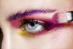 Fermez-vous sur des yeux, en faisant les fards à paupières et l'eye-liner colorés Photos libres de droits