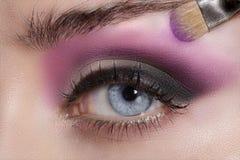 Fermez-vous sur des yeux, en faisant les fards à paupières et l'eye-liner colorés Images libres de droits
