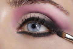 Fermez-vous sur des yeux, en faisant les fards à paupières et l'eye-liner colorés Image stock