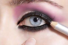 Fermez-vous sur des yeux, en faisant les fards à paupières et l'eye-liner colorés Photo libre de droits