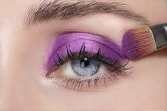 Fermez-vous sur des yeux, en faisant les fards à paupières et l'eye-liner colorés Photos stock