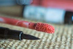 Fermez-vous sur l'applicateur liquide de rouge à lèvres sans compter que l'eye-liner photos stock