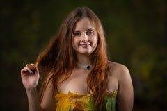 Fermez-vous sur la jeune fille attirante avec la robe de port de longs cheveux faite à partir des feuilles colorées dans la forêt photo libre de droits