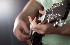 Fermez-vous sur la main du ` s de l'homme jouant la guitare Images stock