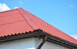 Fermez-vous sur la maison rouge de construction de toiture avec le système de gouttière de toit Photo libre de droits