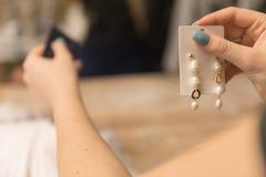 Fermez-vous sur la photo, la fille paye avec une carte dans le magasin des boucles d'oreille image stock