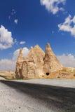 Fermez-vous sur la route vide avec les troglodytes renversants se levant en ciel bleu, cappadocia, dinde Images stock