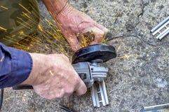 Fermez-vous sur la scie électrique et les mains, équipent le travail avec la broyeur, étincelles volent Photo stock