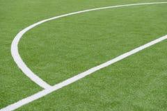 Fermez-vous sur le terrain de football avec l'herbe artificielle et les rayures blanches photo stock