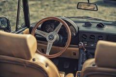 Fermez-vous sur le vieux volant de vintage et habitacle d'Apha Romeo Photos libres de droits
