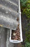 Fermez-vous sur les feuilles et la saleté dans la gouttière de toit d'amiante Photos libres de droits