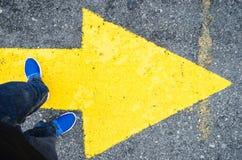 Fermez-vous sur les jambes d'une position d'homme sur une flèche jaune dans la direction vers la droite, concept des décisions da photo libre de droits