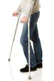 Fermez-vous sur les jambes masculines avec des béquilles Image stock