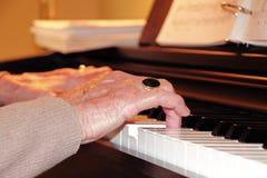 Fermez-vous sur les mains et le piano de la femme supérieure Photos stock