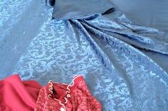 Fermez-vous sur les pyjamas rouges de femme sur le lit malpropre Photos stock